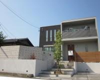 打ち放しコンクリートの外壁を持つ家に、空洞ブロックを合わせてデザインしたエクステリア