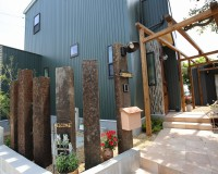 三重県河芸町中別保にて新築した住宅の外観。モスグリーンの外観に。枕木とパーゴラで外構を作っています。